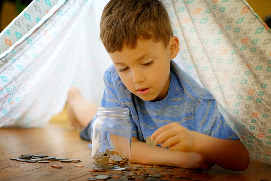 Young boy counting money on the floor